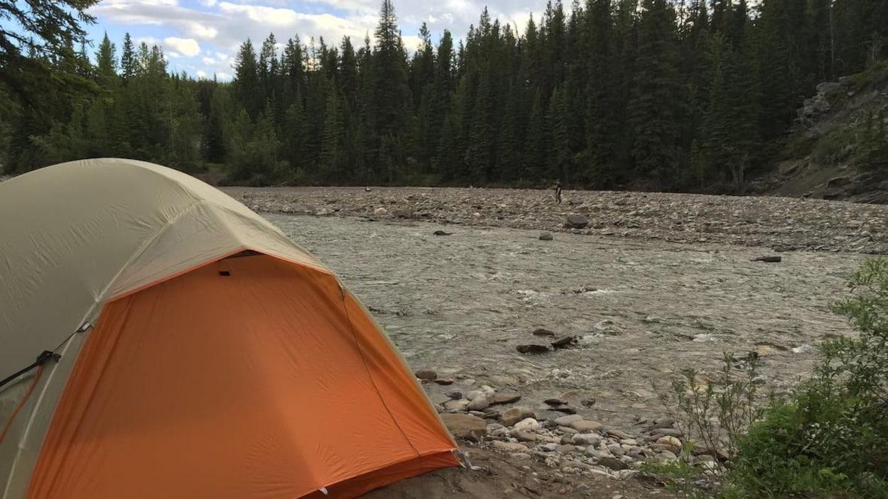 Une tente est plantée à côté d'une rivière. Il y a des conifères en arrière-plan.