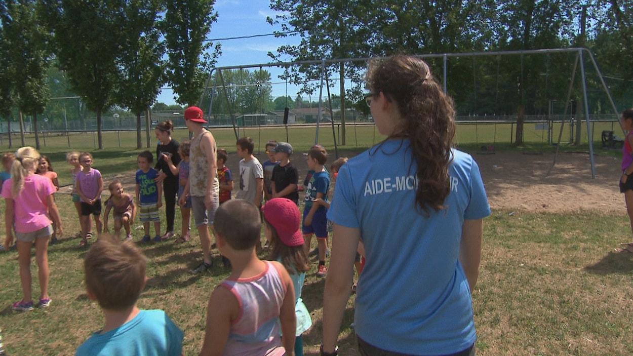 Une monitrice tourne autour d'un groupe d'enfants dans un parc.
