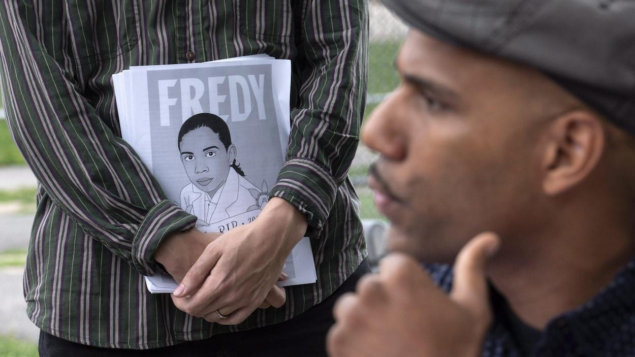 Un homme se tient le menton devant une personne tenant des affichettes représentant Fredy Villanueva.