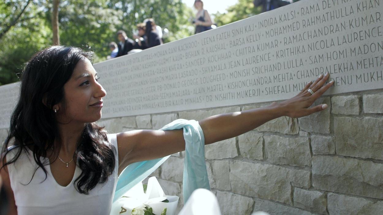 Une femme devant une pierre