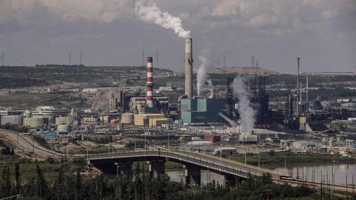 Dans l'image, des fumées qui s'échappent des usines dans la région de Fort McMurray
