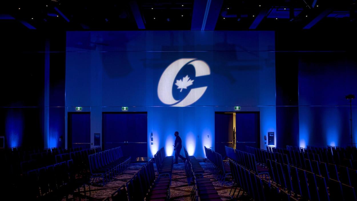 Un homme, de loin, marche devant un drapeau du Parti conservateur du Canada avant l'ouverture du congrès du parti en août 2018 à Halifax.