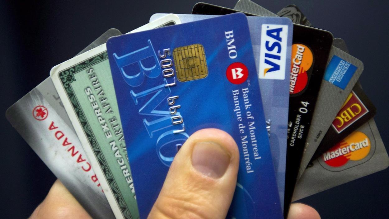 Une personne tient dans sa main diverses cartes de crédit.