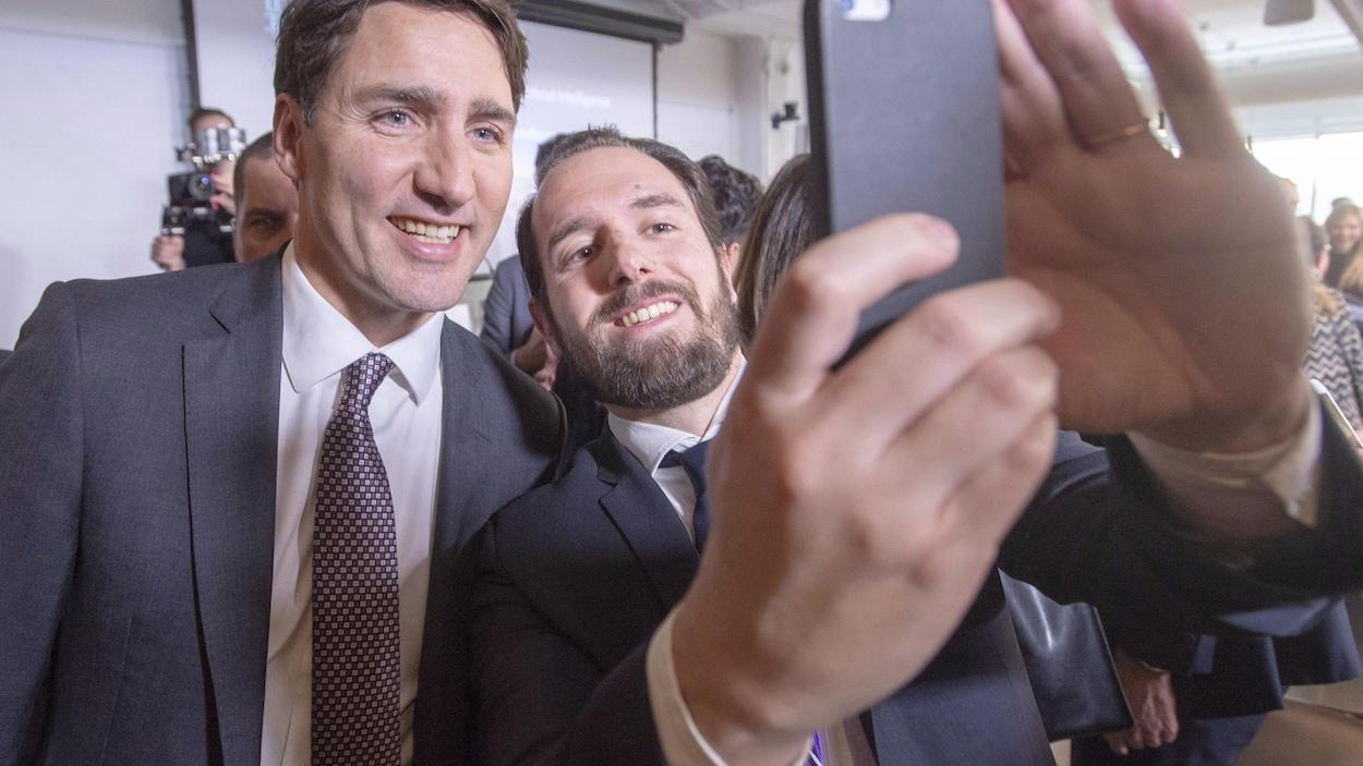 Le premier ministre Justin Trudeau posant pour un égoportrait avec un jeune homme barbu. Les deux hommes portent un veston-cravate.