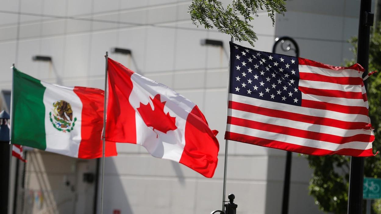 Trois drapeaux différents flottent près d'un bâtiment lors d'une journée ensoleillée.