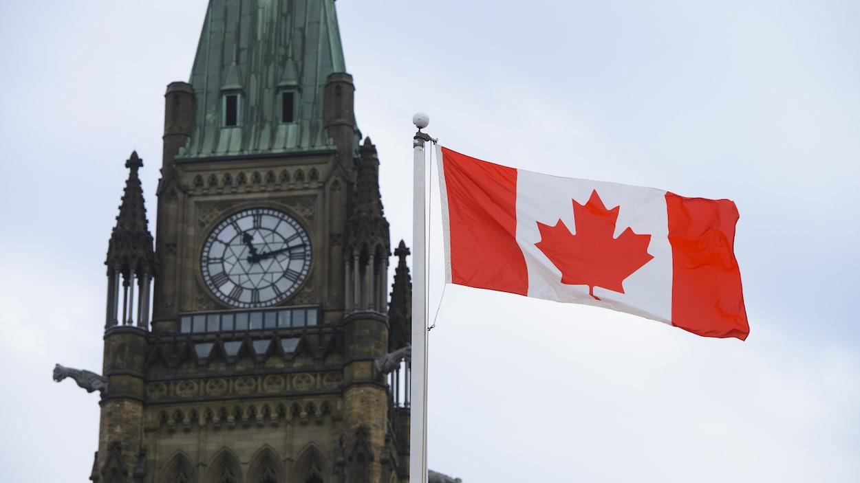 Un drapeau flotte devant le parlement à Ottawa.