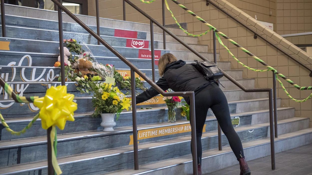 Une femme dépose une gerbe de fleurs à l'aréna Elgar Petersen, où jouent les Broncos de Humboldt.