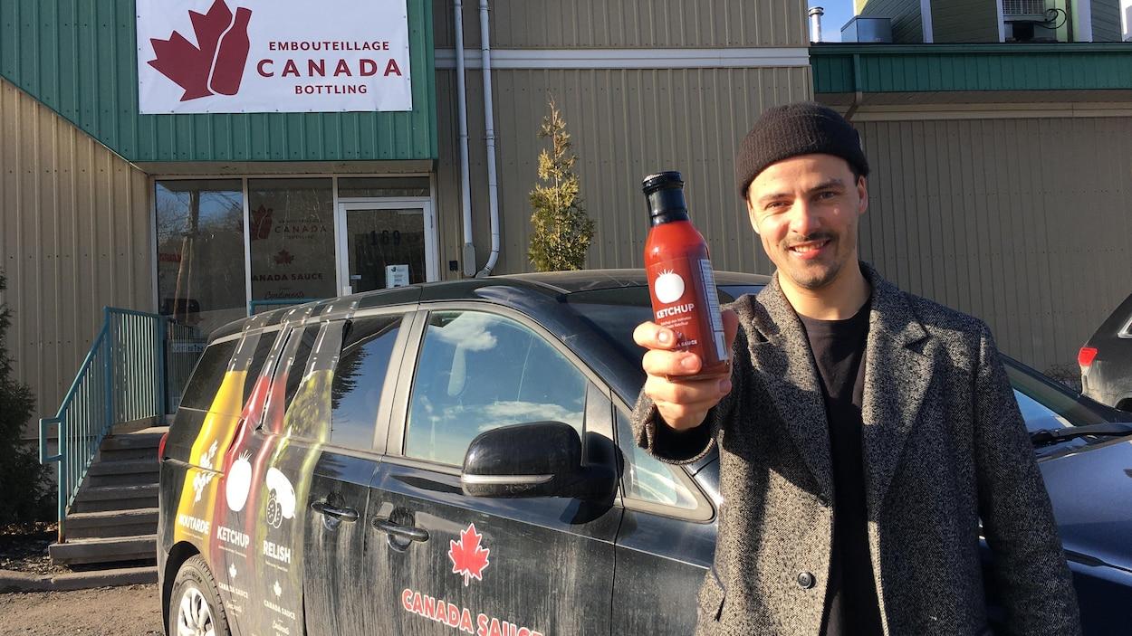 Un homme tient une bouteille de ketchup devant un véhicule stationné devant un commerce d'embouteillage.