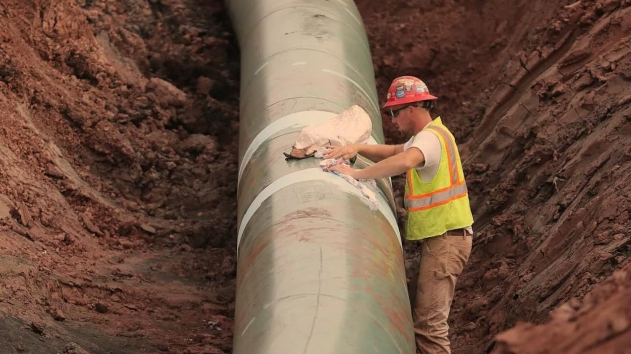 Un travailleur installe un pipeline.