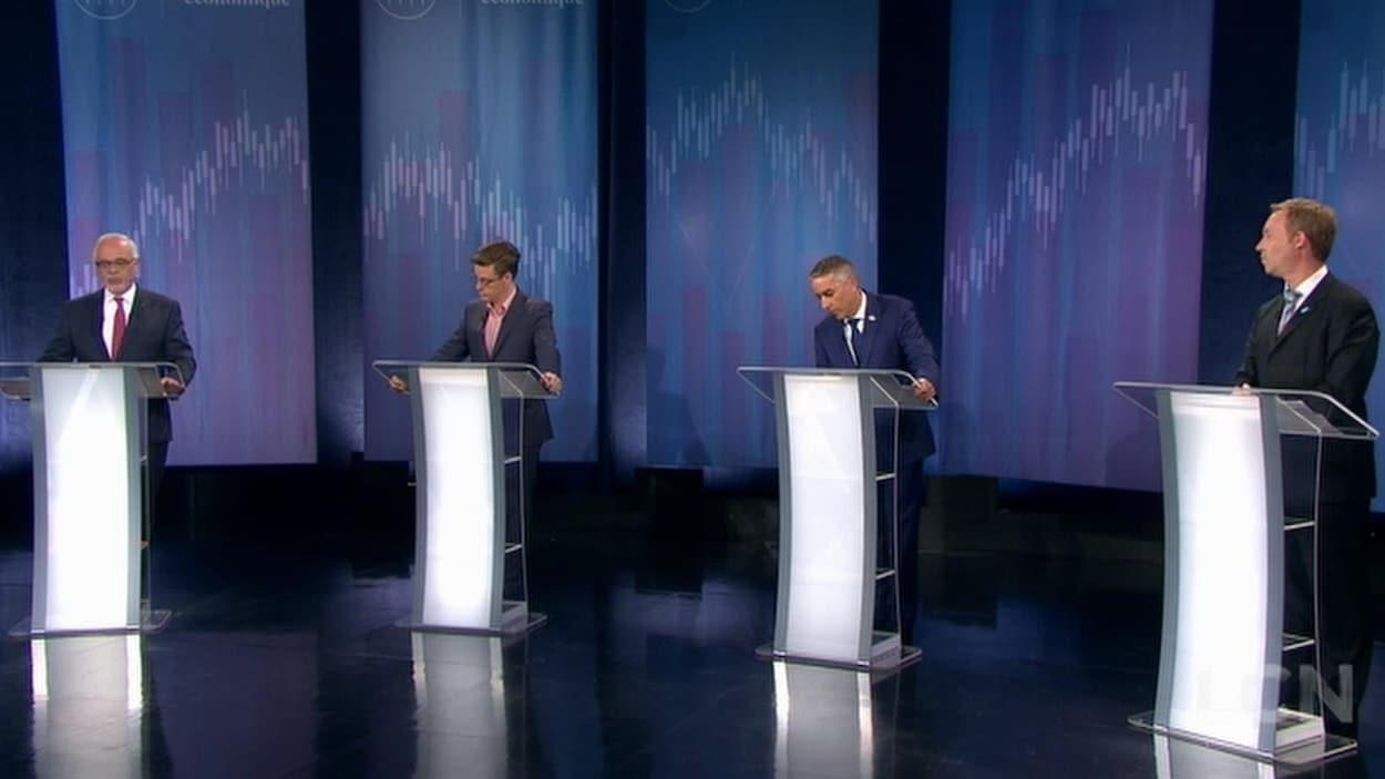 Les quatre candidats se tenant derrière leur podium respectif.