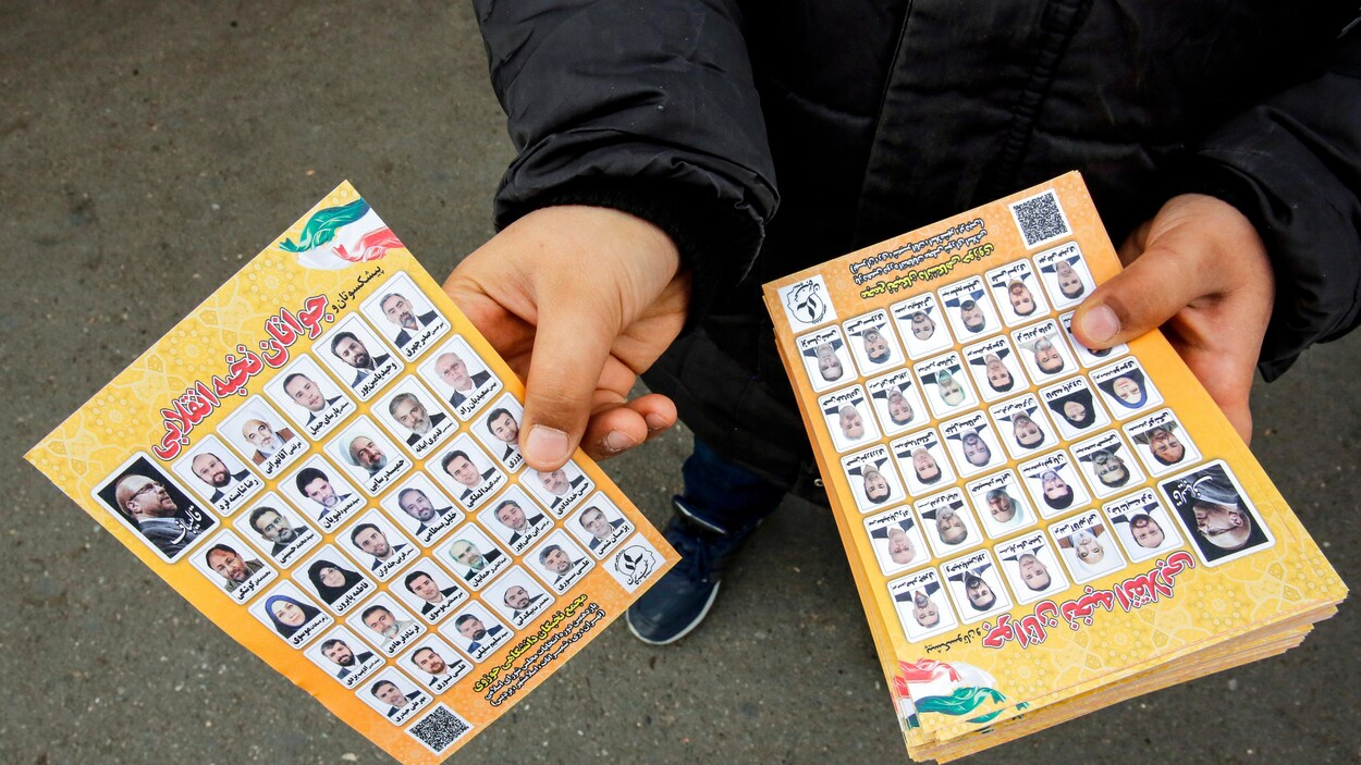 Un homme tend un dépliant avec les photos de 30 candidats.