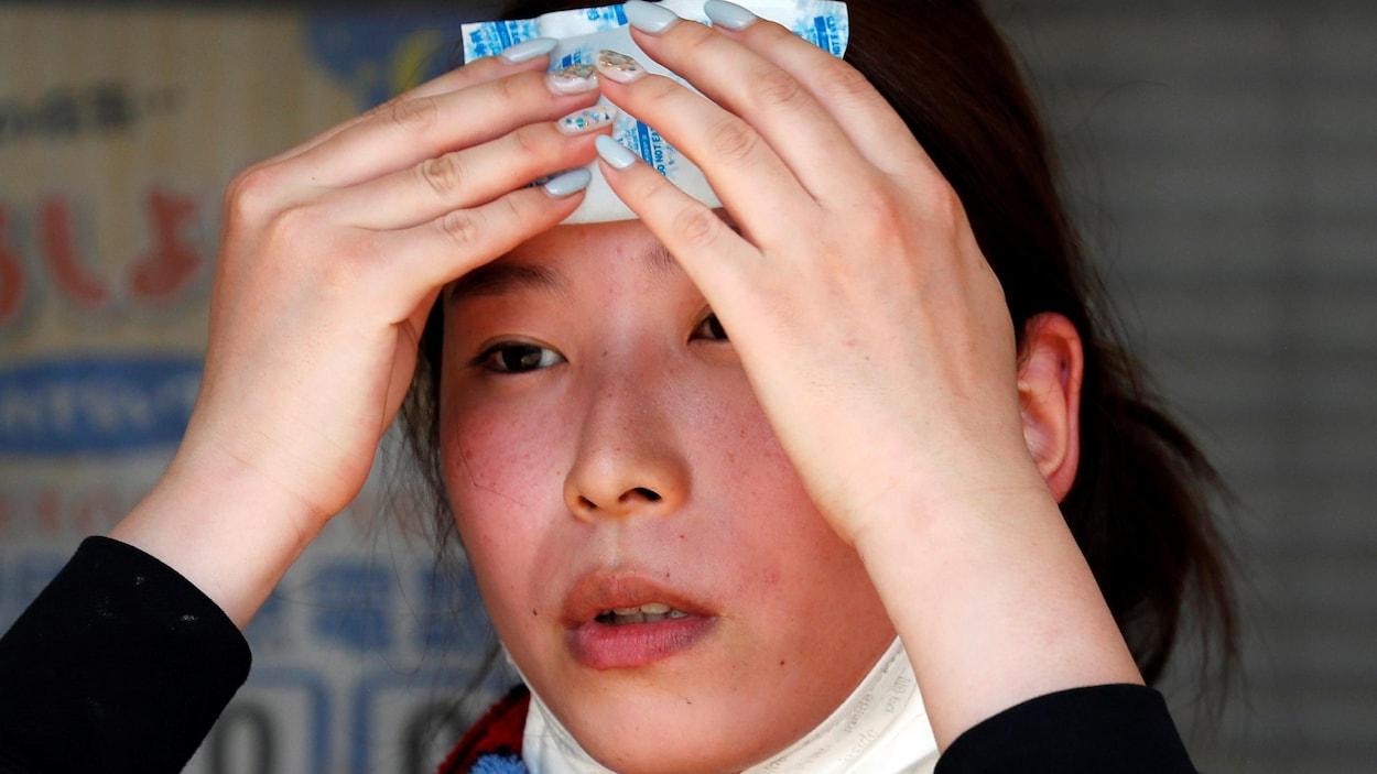 Une Japonaise se rafraîchit avec un paquet réfrigérant