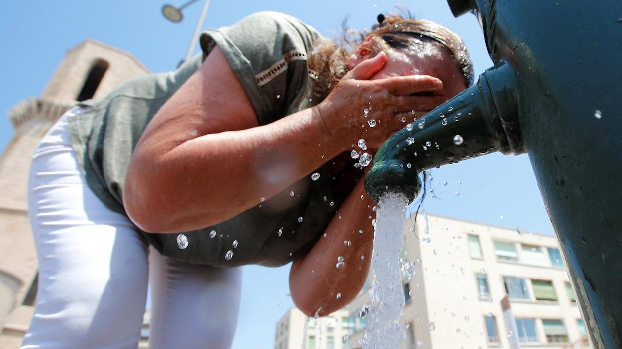 Une femme penchée devant une fontaine se mouille la figure.