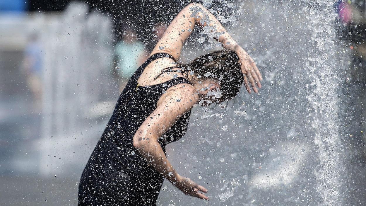 Une femme se rafraîchit dans une fontaine, à Montréal, pendant la canicule.