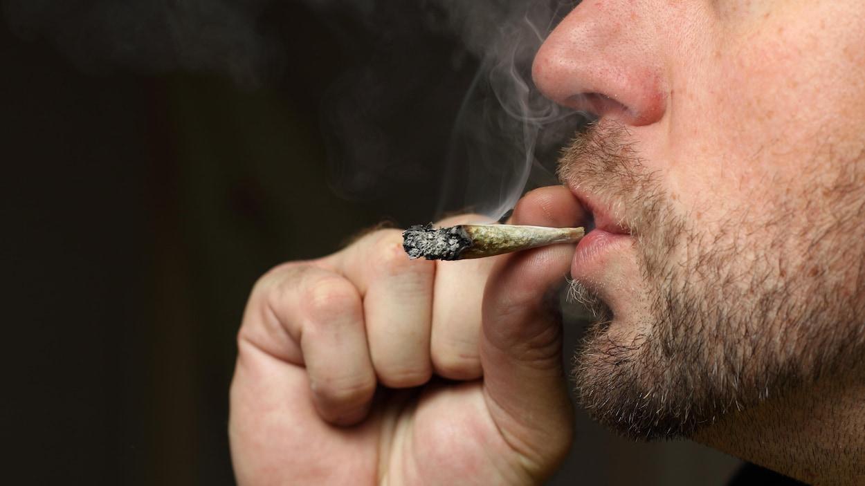 Un homme consomme du cannabis.