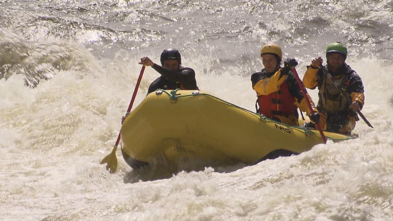 Trois personnes descendent une rivière en rafting.