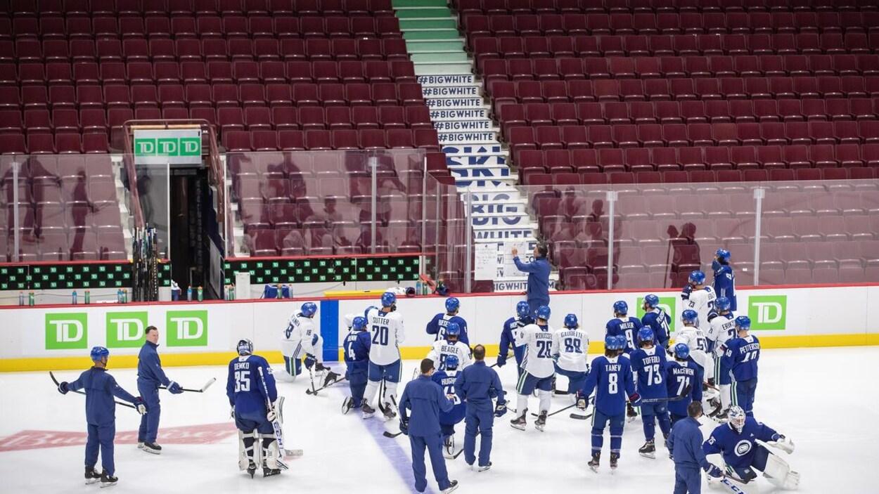 Les joueurs des Canucks autour de leur entraîneur-chef Travis Green sur la patinoire.