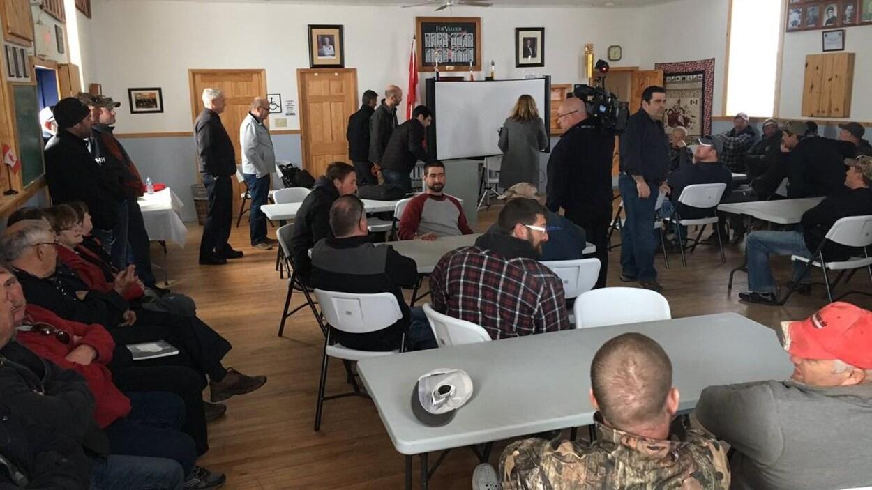 Des hommes assis dans une salle