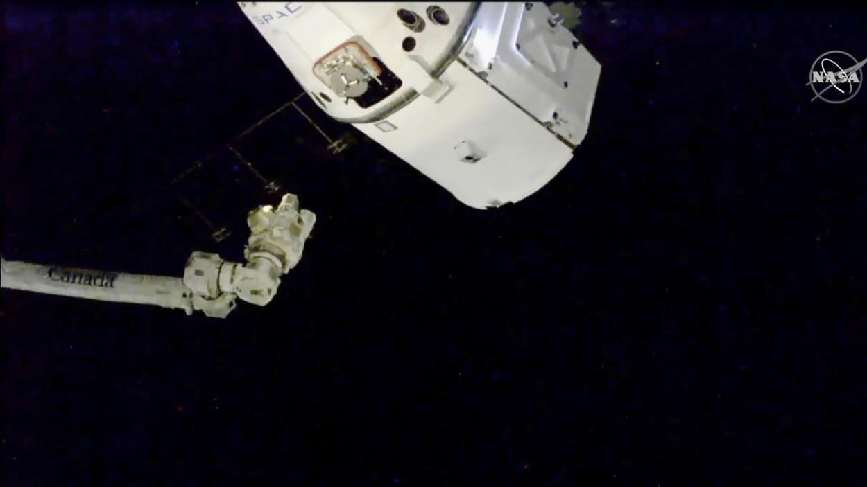 Une capsule spatiale à proximité du bras robotisé de la Station spatiale internationale