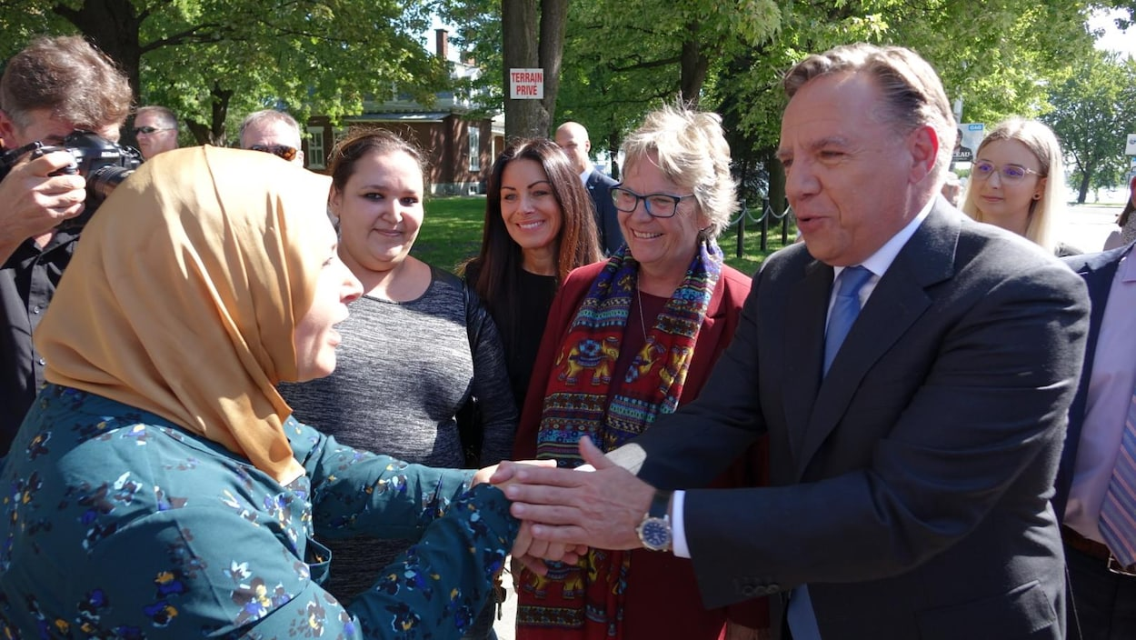 Entourés, le chef de la Coalition avenir Québec serre la main d'une électrice.