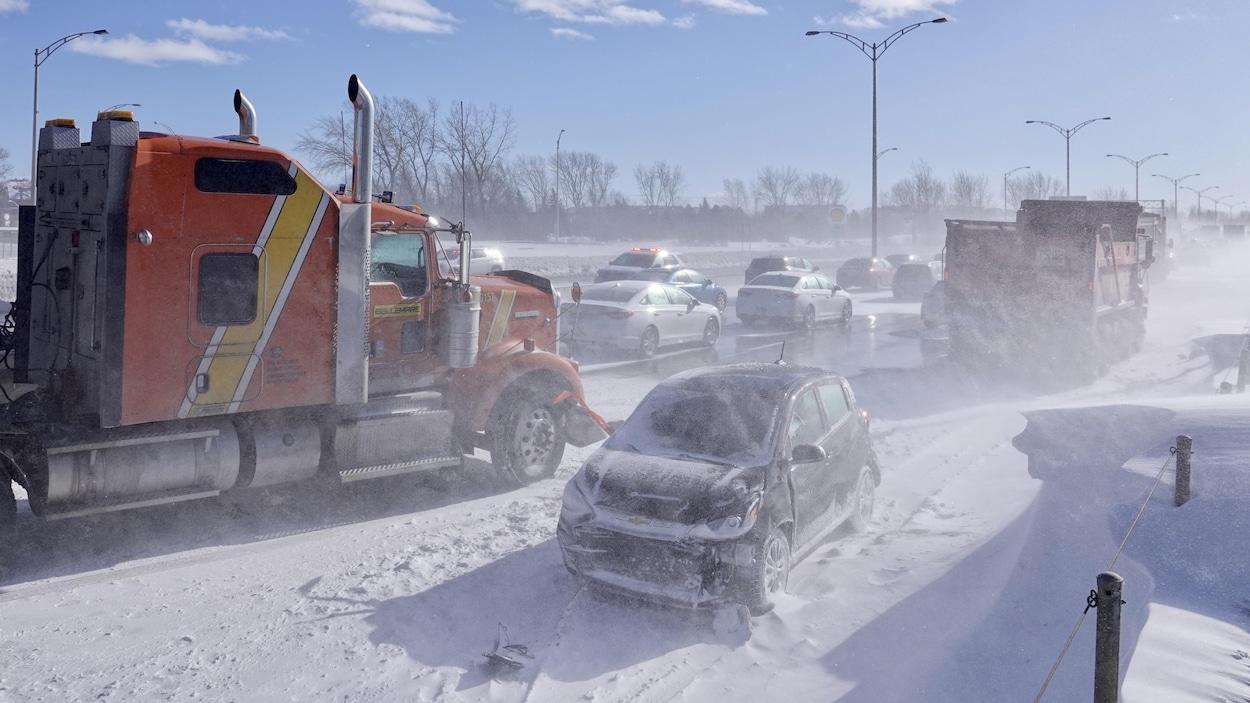 Des camions et une voiture endommagée sur le bord d'une route enneigée.