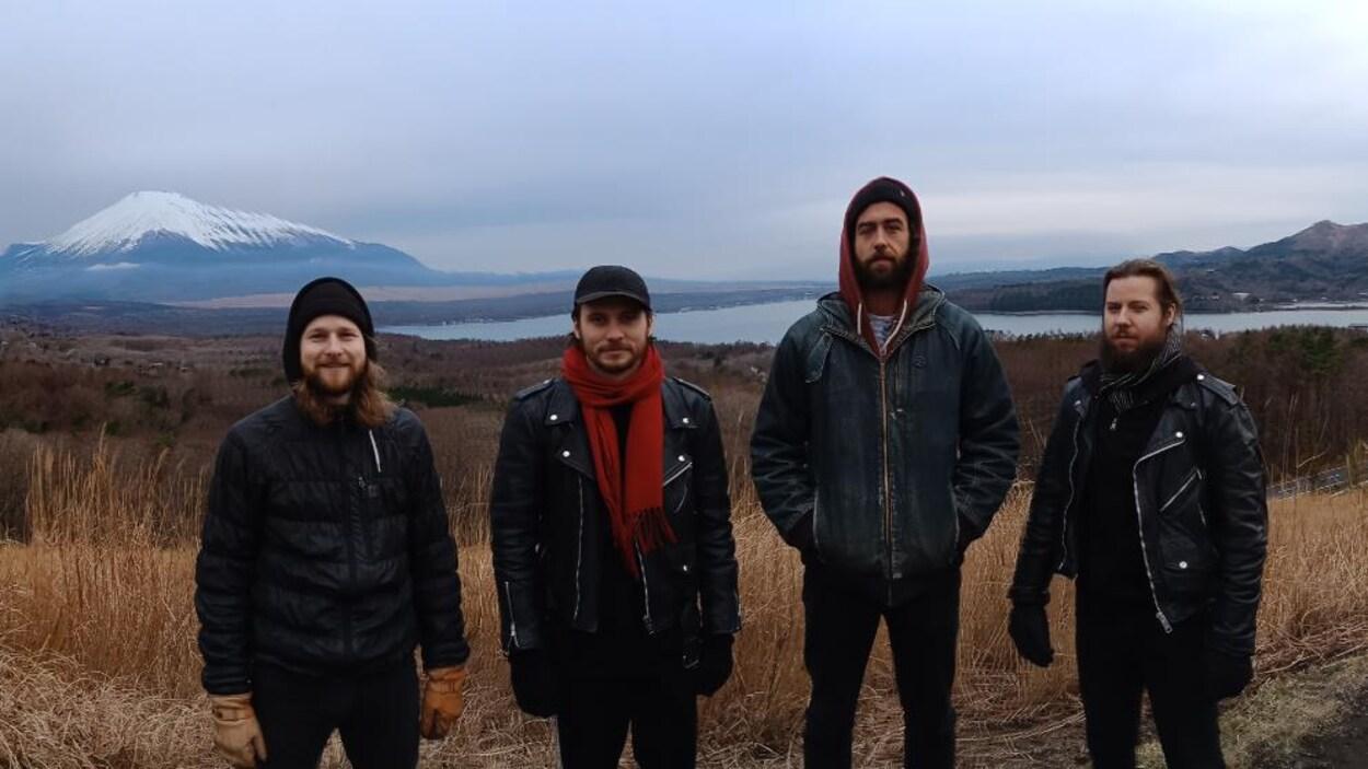 Quatre jeunes hommes se tiennent devant un paysage formé d'un lac avec une montagne enneigée en arrière-plan.