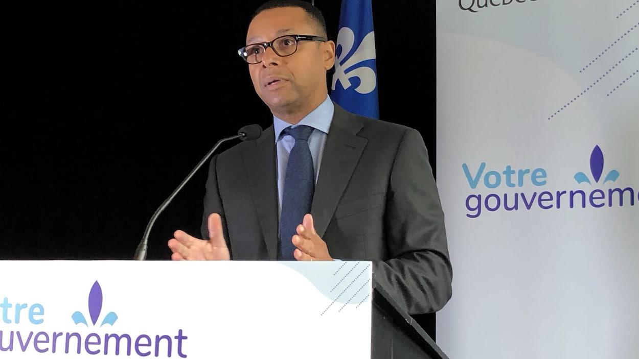 Le ministre Lionel Carmant devant un lutrin.