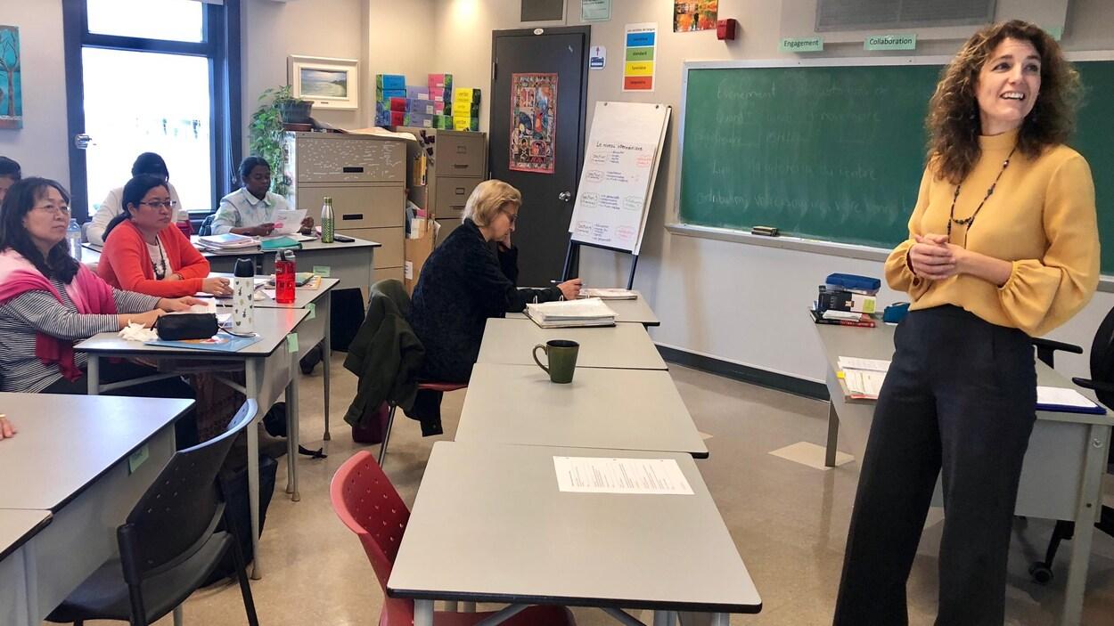 À droite, Caroline Chayer debout devant un tableau. Devant elles, des étudiants la regardent, certains prennent des notes.