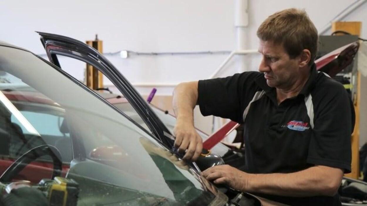 Un homme installe un pare-brise sur une auto.