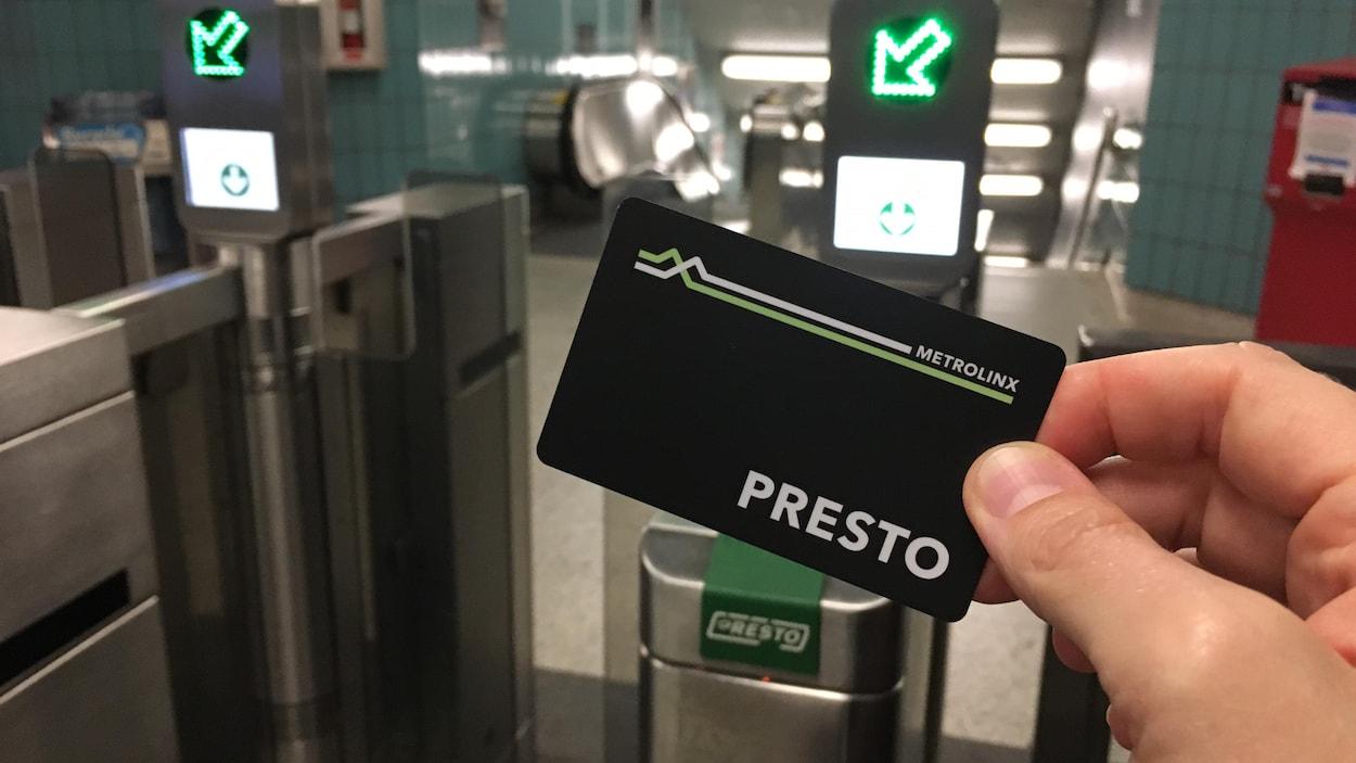 Photo d'une carte noire portant le logo « Presto » devant une porte d'entrée du métro.