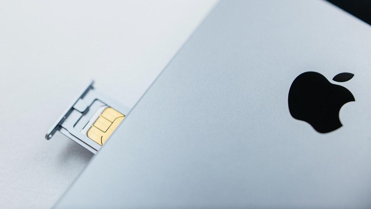 Le boîtier d'un iPhone SE, avec sa carte SIM exposée.
