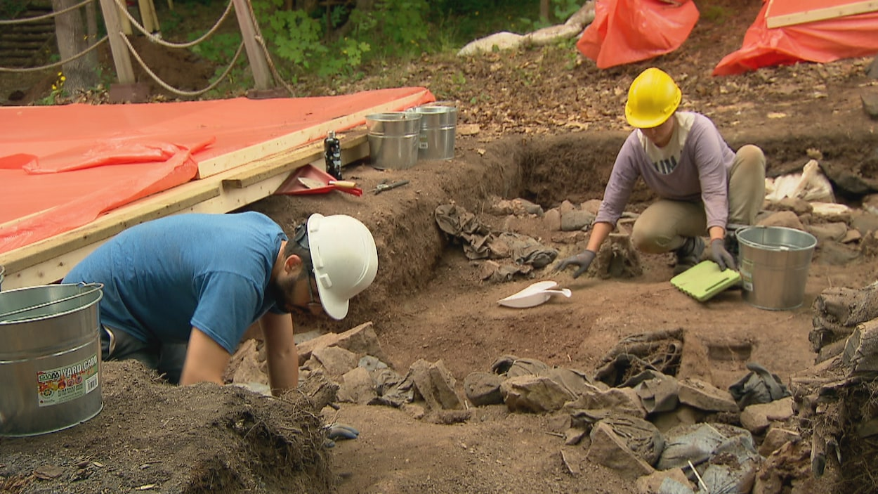 Deux archéologues procèdent au nettoyage d'un carré de fouilles du site Cartier-Roberval à Québec.
