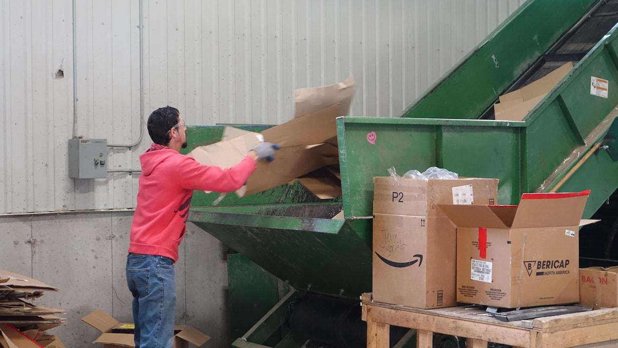 Un employé place du carton sur un convoyeur.