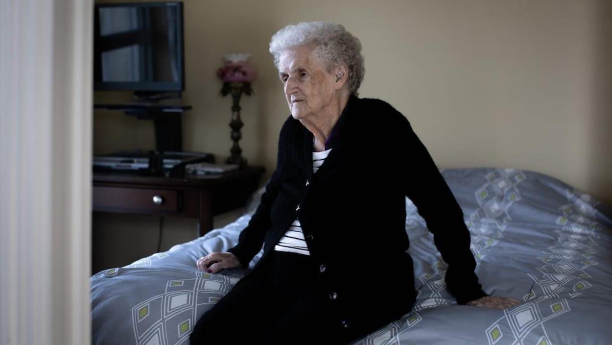 Rita Bedford assise sur son lit.