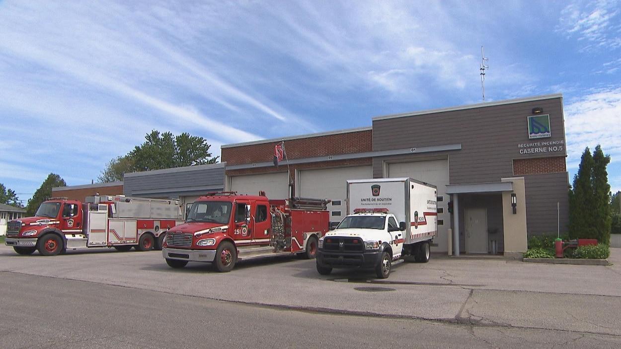 Deux camions de pompier et un troisième portant l'inscription « Unité de soutien » sont stationnés devant une caserne sur laquelle on voit clairement le logo de la Ville de Trois-Rivières.
