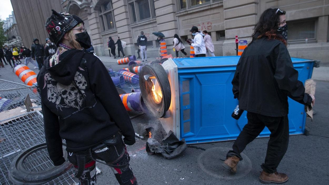Deux manifestantes se tiennent près d'une toilette portative en feu.