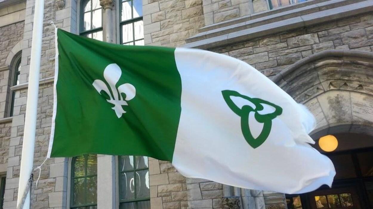 Un drapeau vert et blanc flotte au vent.