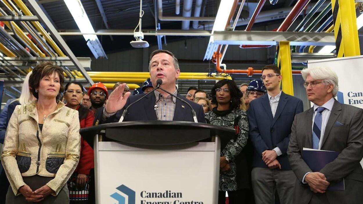 Jason Kenney s'exprime au pupitre lors d'une déclaration ayant lieu au Centre de l'energie canadienne. Sur le pupitre, le logo est visible.