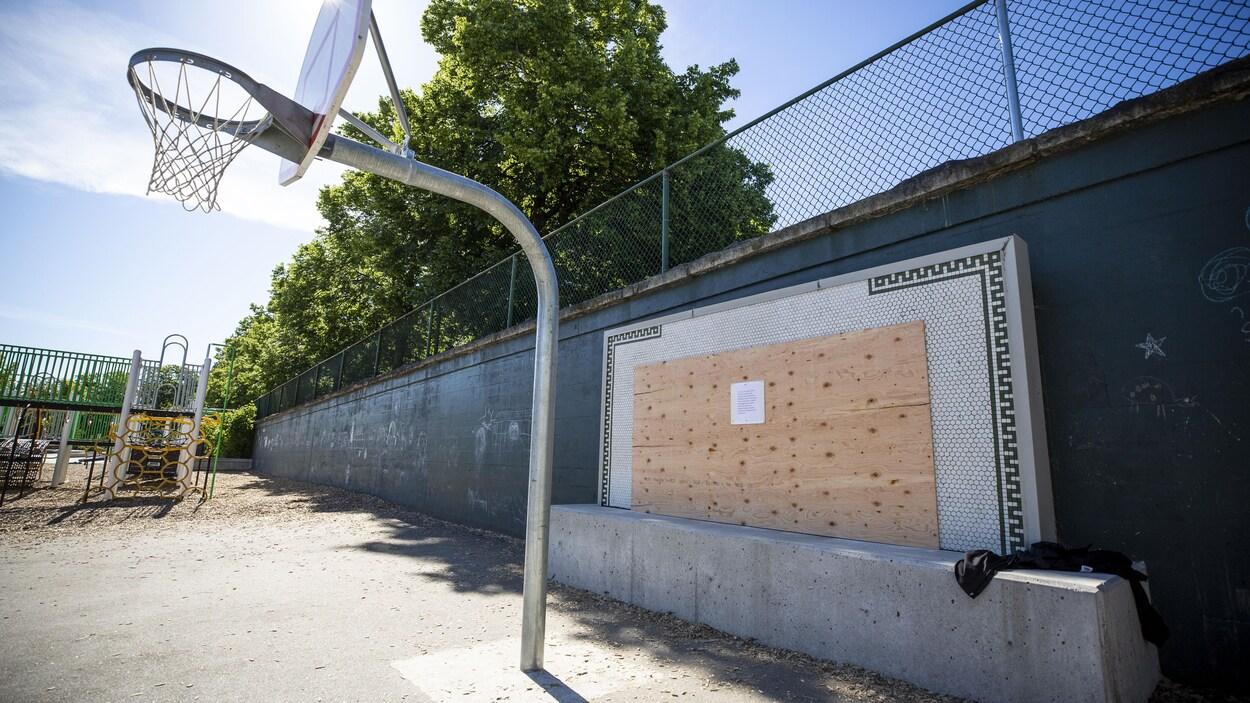 Un panneau en bois est apposé sur une plaque en mosaïque,  derrière un panier de basketball dans une cour d'école.