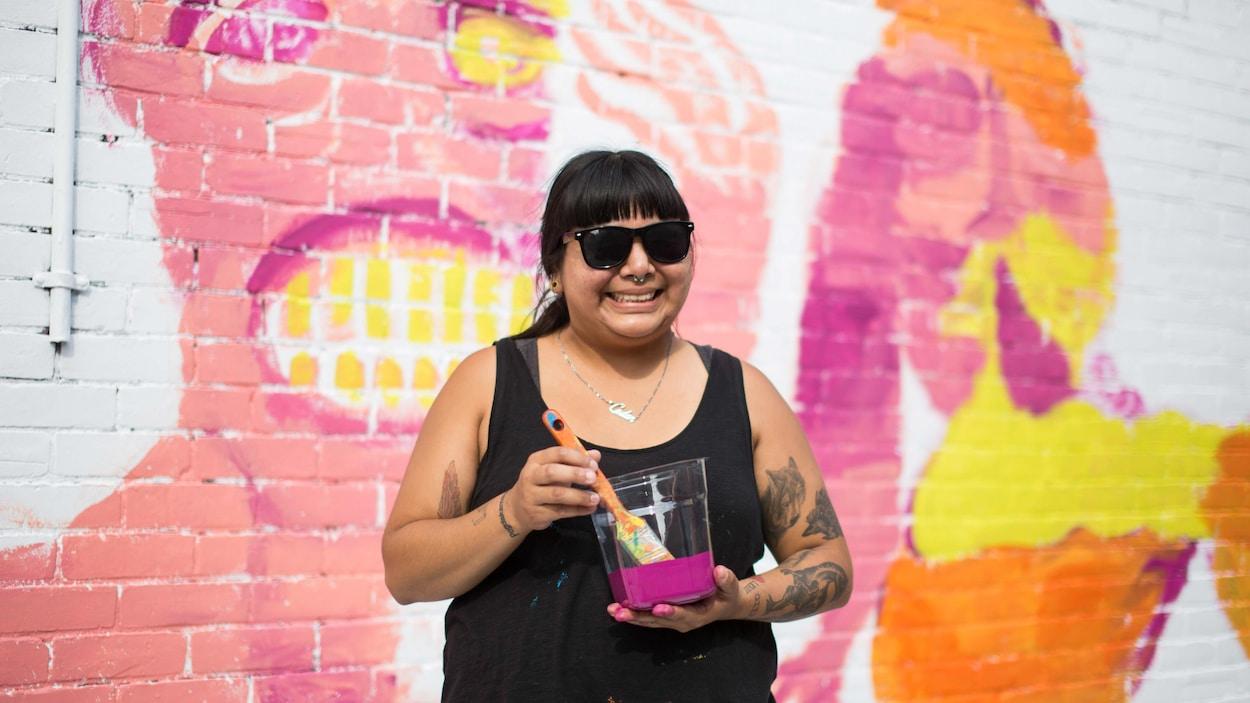L'artiste Cedar Eve Peters devant sa murale