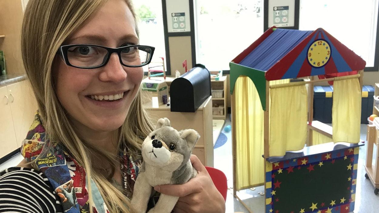 Cédelynne Lachance pose dans la garderie Les P'tits loups à Saint-Georges au Manitoba. Elle tient une peluche en forme de loup dans l'une des ses mains.