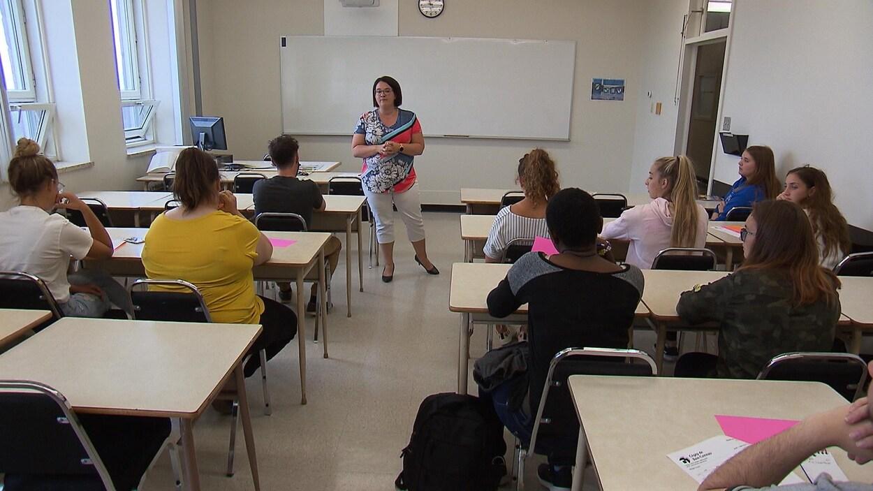 La professeure est debout au milieu d'une rangée de bureaux.
