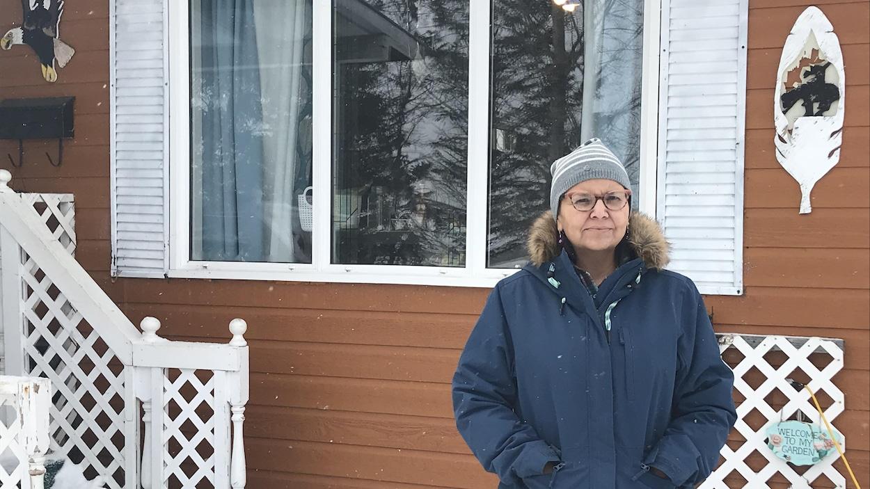 Une femme portant un manteau bleu et des lunettes est devant une maison.