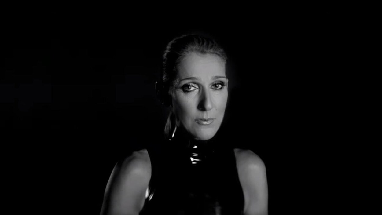 La chanteuse regarde la caméra en versant une larme.