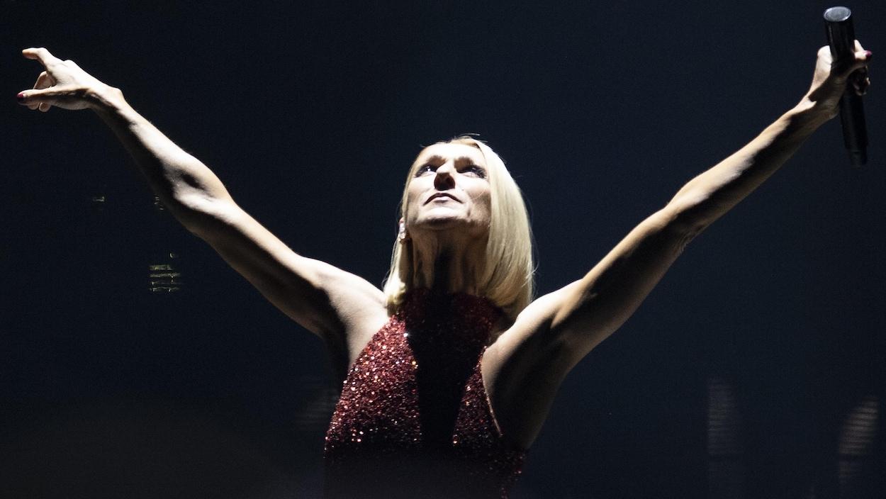 Céline Dion, sur scène, porte une robe rouge.