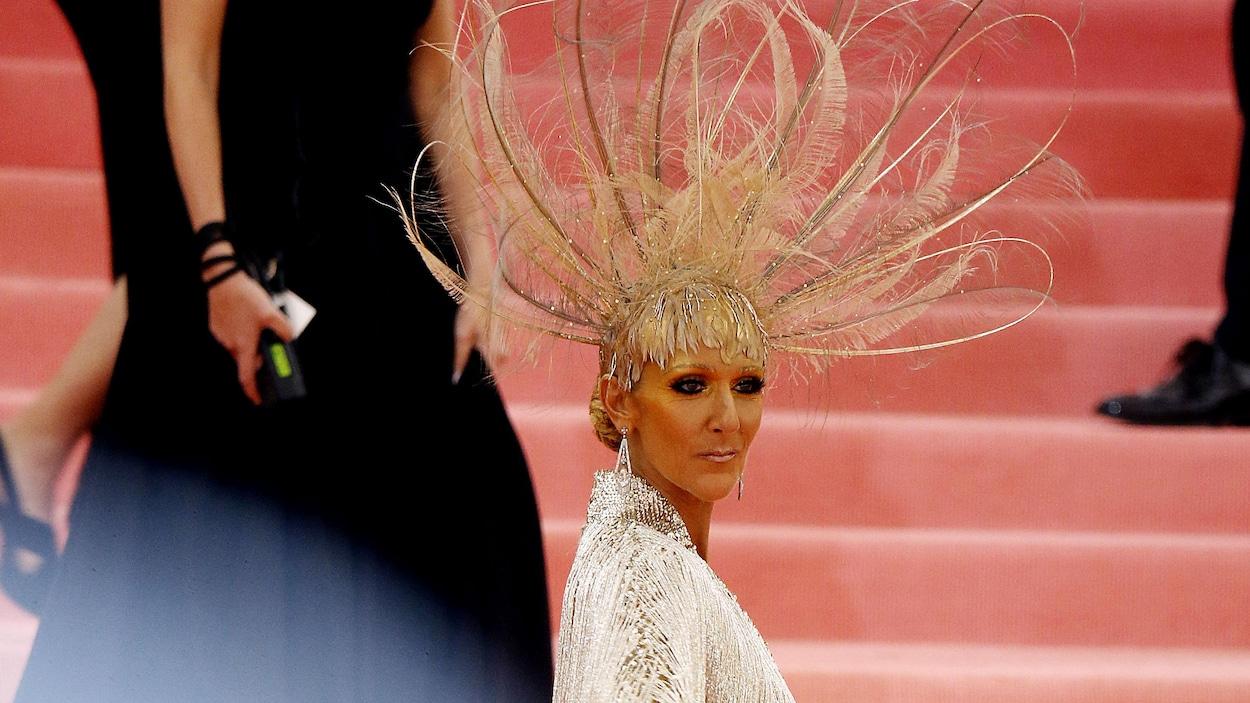 La chanteuse pose de dos avec une coiffe dorée en plumes et une robe de couleur argent.