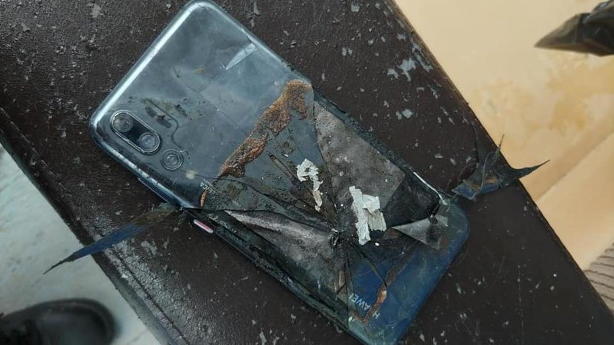 Téléphone cellulaire calciné sur une terrasse extérieure.