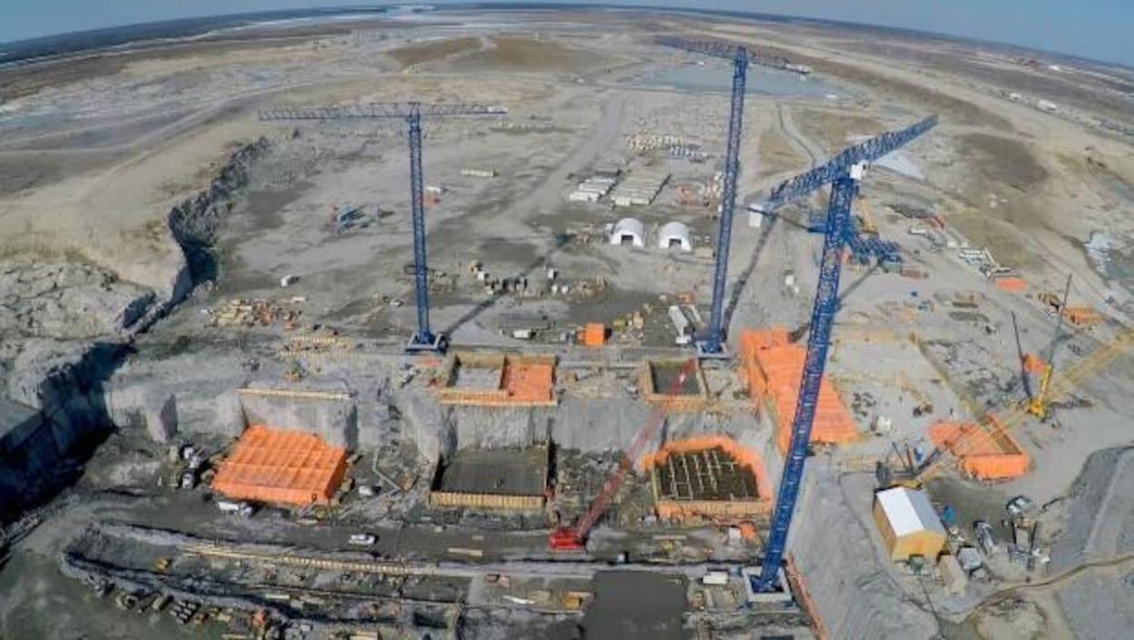Vue aérienne d'un chantier de construction sur lequel se trouvent, entre autres, trois grues.