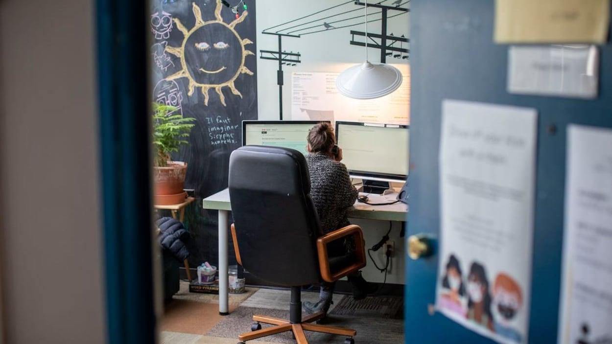 Une femme, que l'on aperçoit de dos, parle au téléphone dans un bureau d'un centre de crise à Vancouver.
