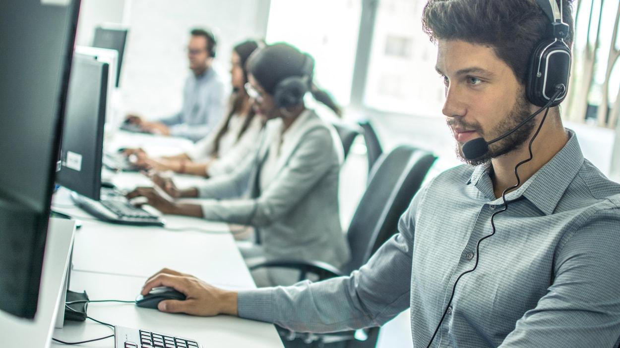 Un jeune homme travaille dans un centre d'appel avec d'autres personnes assises derrière des bureaux.